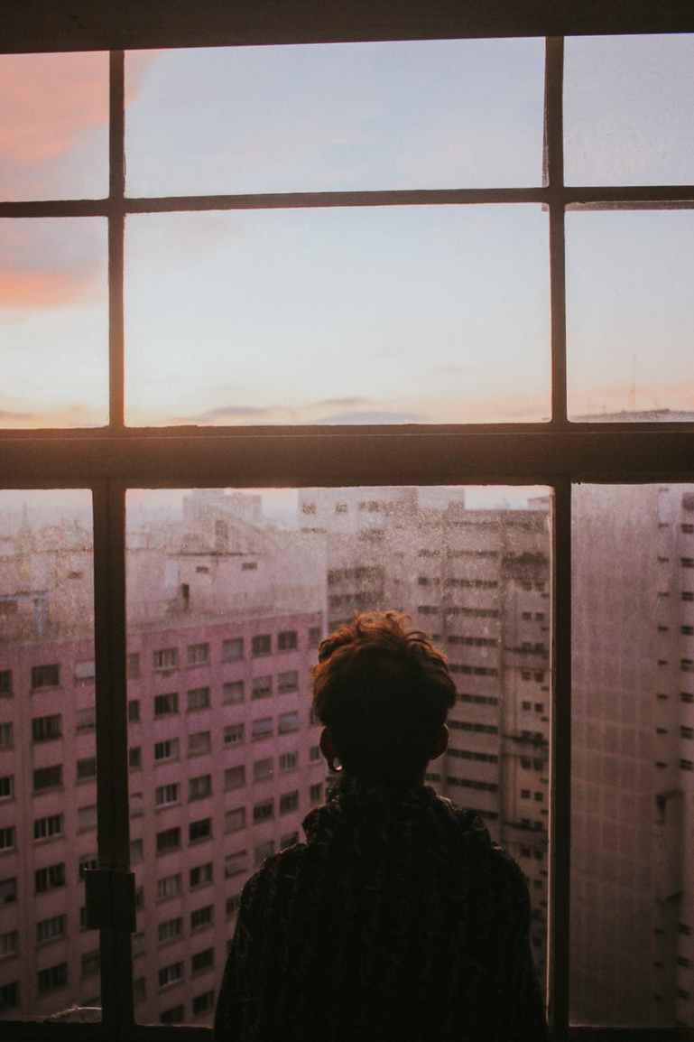 man standing near glass window looking outside