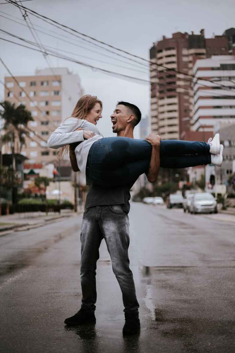 man carrying woman in the middle of street